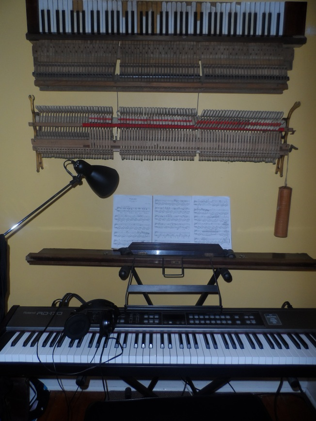 There is an old piano on the wall and a functional keyboard on the foreground. Very artistic.